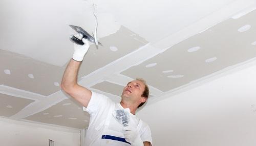 Plasterer plastering ceiling
